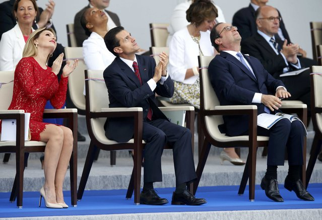 French President Francois Hollande (R), Mexico's President Enrique Pena Nieto (C) and Mexico's First Lady Angelica Rivera applaud during the traditional Bastille Day military parade in Paris, France, July 14, 2015. (Photo by Charles Platiau/Reuters)