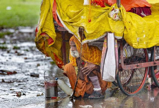 A Sadhu, or Hindu holy man, takes shelter from the rain under a cart in Prayagraj, in the northern Indian state of Uttar Pradesh, Saturday, September 28, 2019. (Photo by Rajesh Kumar Singh/AP Photo)