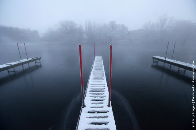 A snow-covered jetty in a partially frozen River Great Ouse