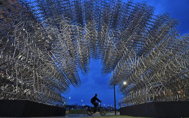 "A man rides his bike past an art installation entitled ""Forever Cycles"" by Chinese artist Ai Weiwei in Rio de Janeiro, Brazil, on August 19, 2019. The installation is comprised of over 1000 stainless steel bicycles and is part of Ai Weiwei's exhibition, which opens in Rio de Janeiro on August 21, 2019. (Photo by Carl De Souza/AFP Photo)"
