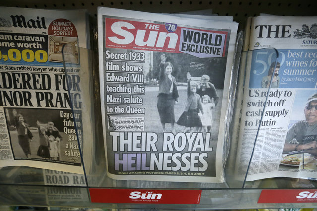 A row of newspapers on display including a paper with a photo of Britain's Queen Elizabeth as a child giving a Nazi salute,  in a shop, in London, Saturday July 18, 2015. Buckingham Palace has expressed its disappointment with a tabloid newspaper for publishing images of a young Queen Elizabeth II performing a Nazi salute together with her family in 1933, the year Adolf Hitler came to power. (Photo by Tim Ireland/AP Photo)