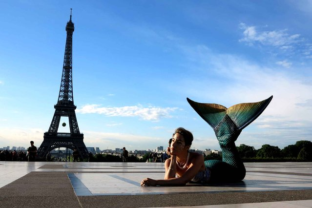 A model dressed as a mermaid poses in front of the Eiffel Tower during sunrise on May 22, 2014 in Paris. (Photo by Ludovic Marin/AFP Photo)