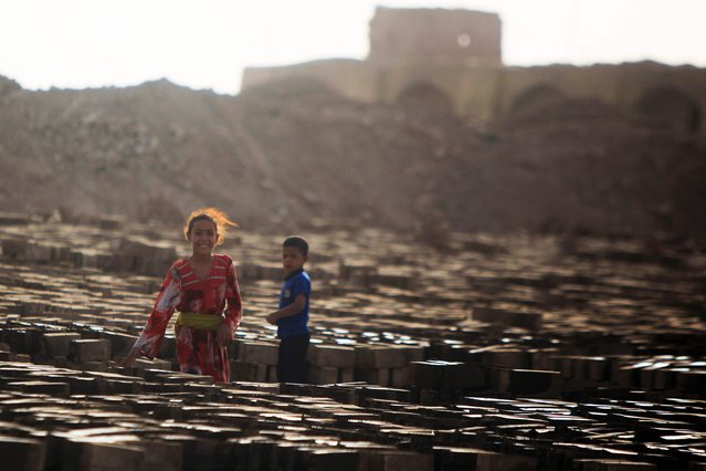 Iraqi children stand amid bricks baking dry in the sun at a brick factory near the central Iraqi shrine city of Najaf on May 16, 2017. (Photo by Haidar Hamdani/AFP Photo)