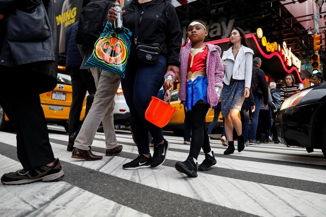 A child dressed in costume for Halloween crosses through Times Square during the evening rush in Manhattan, in New York City, October 31, 2019. (Photo by Brendan McDermid/Reuters)
