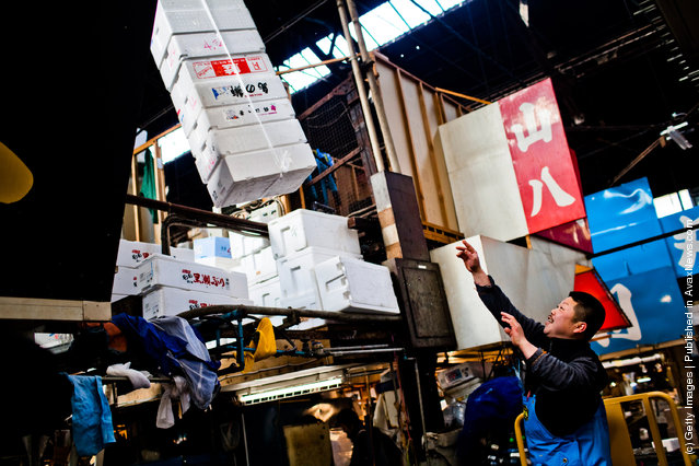 A worker throws empty ice boxes up to be stored at the Tsukiji fish market