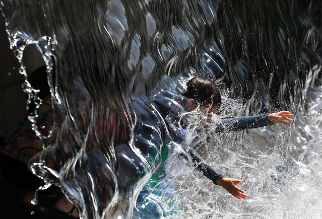 Conan Jones, 5, jumps through a waterfall feature at the Yards Park on Thursday May 18, 2017 in Washington, DC. Temperatures Thursday were expected to reach near 90 degrees. (Photo by Matt McClain/The Washington Post)