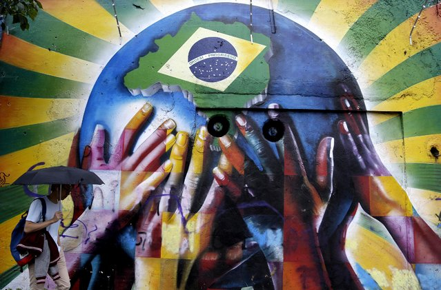 A pedestrian passes graffiti depicting human hands holding the earth with the Brazilian flag in Sao Paulo. (Photo by Thanassis Stavrakis/Associated Press)