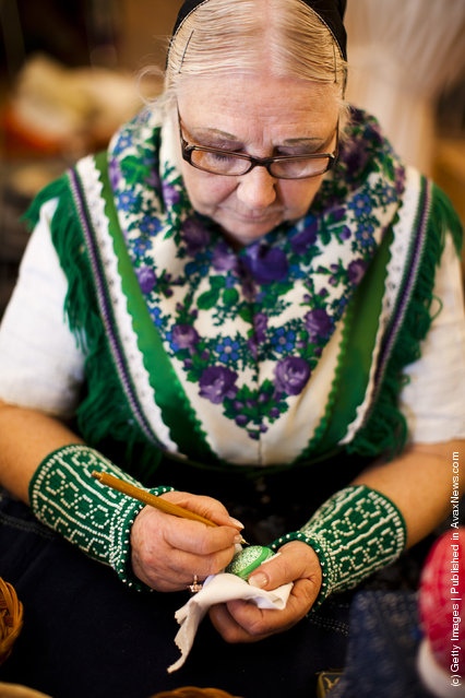 Ute Zschieschang from the village Bergen, wearing a traditional Lusatian sorbian folk dress, paints an Easter egg in traditional Sorbian motives at the annual Easter egg market
