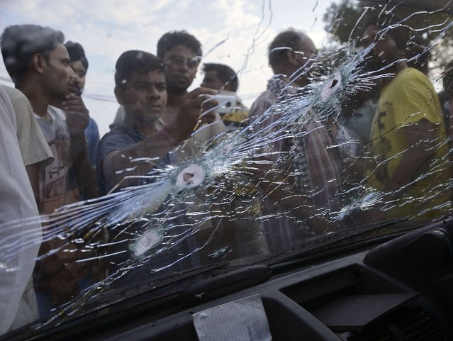 Bullet holes are seen on the windscreen of a car that was damaged in a gunfight in Dinanagar town in Gurdaspur district of Punjab, India, July 27, 2015. (Photo by Mukesh Gupta/Reuters)