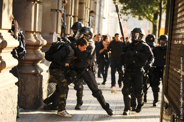 Riot police clash with a demonstrator during heavy clashes with demonstrators during a 24-hour strike on March 29, 2012 in Barcelona, Spain