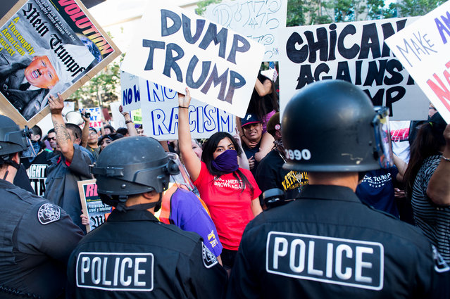 Police form a line to contain protesters outside a campaign rally for Republican presidential candidate Donald Trump on Thursday, June 2, 2016, in San Jose, Calif. A group of protesters attacked  Trump supporters who were leaving the presidential candidate's rally in San Jose on Thursday night. A dozen or more people were punched, at least one person was pelted with an egg and Trump hats grabbed from supporters were set on fire on the ground. (Photo by Noah Berger/AP Photo)