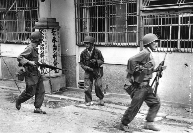 South Korean troops in the streets of Inchon with guns at the ready, following the invasion of the town by United Nations forces, 1950