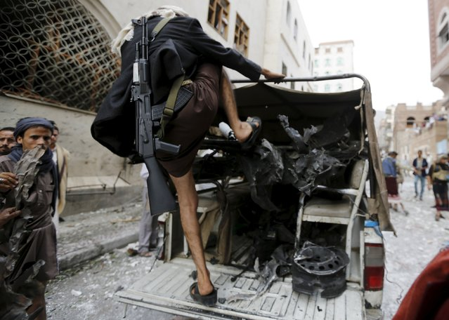 Houthi militants collect parts of a car that exploded outside an Ismaili mosque in Yemen's capital Sanaa July 29, 2015. A car bomb exploded outside an Ismaili mosque in Yemen's war-damaged capital Sanaa on Wednesday, killing four people and wounding six, health authorities and a security source said. (Photo by Khaled Abdullah/Reuters)