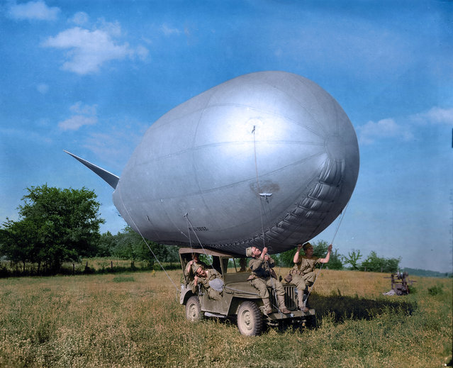Soldiers try to attach the balloon to their car, June 1944. (Photo by Jared Enos/Mediadrumworld.com)