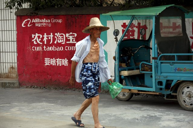 A villager walks past an Alibaba rural service centre in Yuzhao Village, Tonglu, Zhejiang province, China, July 20, 2015. (Photo by Aly Song/Reuters)