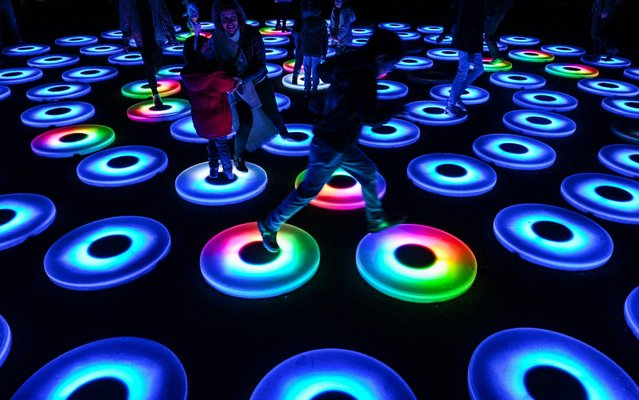 Children with their parents play in an area decorated with lit discs at the Stavros Niarchos Foundation Cultural Centre in Athens, on December 20, 2019. (Photo by Aris Messinis/AFP Photo)
