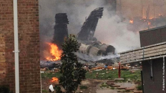 The fuselage of an F/A-18 Hornet smolders after crashing into a residential building in Virginia Beach, Va., April 6, 2012. Authorities said it was miraculous that no one was killed