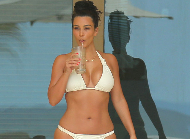 A bikini clad Kim Kardashian cools off with an icy drink while on vacation in Mexico. (Photo by Brian Prahl/Splash News)