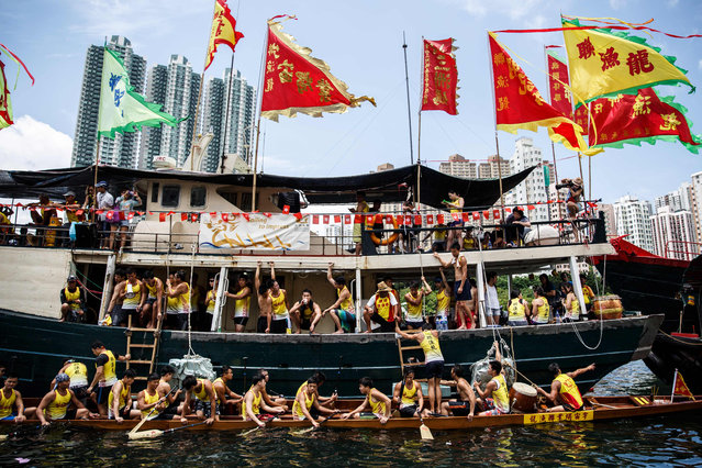 Teammates rest on their host ship above their dragon boat (bottom) during races held to celebrate the Tuen Ng festival in Hong Kong on June 9, 2016. (Photo by Anthony Wallace/AFP Photo)