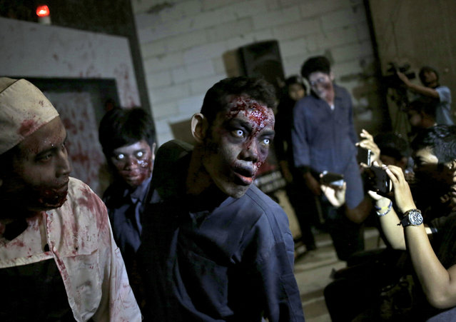 """Reporters use their mobile phones to take pictures of actors dressed as zombies during the opening of """"Dead Prison"""", a zombie-themed performance space at a shopping mall in Jakarta, Indonesia, Friday, June 10, 2016. The attraction, which is run by Indonesia's Zombie Lovers Community was inspired by U.S. television series """"The Walking Dead"""". (Photo by Dita Alangkara/AP Photo)"""