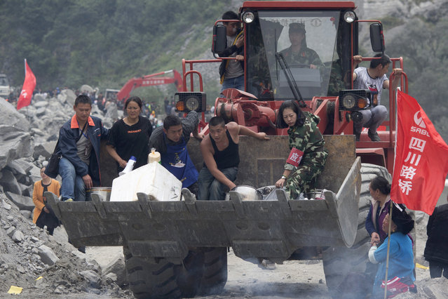 A woman griefs for her relatives as volunteers deliver supplies at the site of a landslide in Xinmo village in Maoxian County in southwestern China's Sichuan Province, Sunday, June 25, 2017. (Photo by Ng Han Guan/AP Photo)