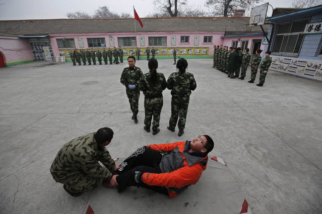 A new student (front) practices sits-up while other students take part in a close-order drill at the Qide Education Center in Beijing February 26, 2014. The Qide Education Center is a military-style boot camp which offers treatment for internet addiction. (Photo by Kim Kyung-Hoon/Reuters)