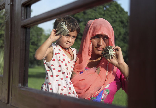 An Indian woman and a child display mortar shells allegedly fired from the Pakistan side at a residential area near the India-Pakistan international border at Kanachack village in Pargwal sector, about 25 kilometers (16 miles) from Jammu, India, Tuesday, August 4, 2015. Indian and Pakistani border guards traded gunfire and mortar shells along their disputed border in the Himalayan region of Kashmir on Tuesday. (Photo by Channi Anand/AP Photo)