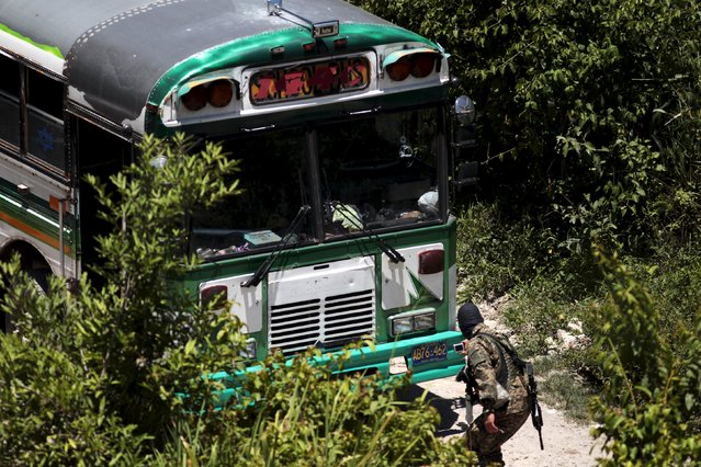 A soldier takes a picture of a bus that was attacked earlier by suspected gang members in San Pedro Perulapan, El Salvador August 5, 2015. (Photo by Jose Cabezas/Reuters)