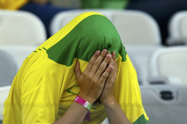 A Brazil fan covers his face after the team's 2014 World Cup semi-finals against Germany at the Mineirao stadium in Belo Horizonte July 8, 2014. (Photo by Ruben Sprich/Reuters)