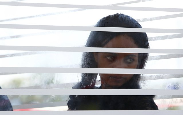 Asylum seeker is pictured behind glass after she was picked up by German police at train station in Rosenheim, southern Germany, August 6, 2015. (Photo by Michaela Rehle/Reuters)