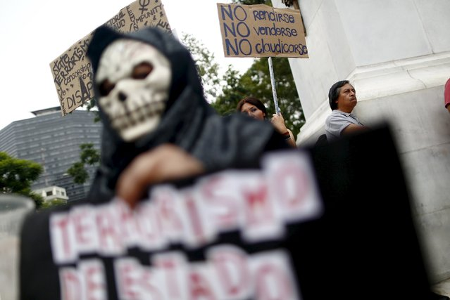 Demonstrators hold sign during a demonstration against the murder of photojournalist Ruben Espinosa and four other women at the Hemiciclo de Juarez monument in Mexico City, August 8, 2015. Espinosa, a prominent Mexican news photographer was among five people found dead in a middle-class neighborhood of the capital on July 31, 2015. (Photo by Edgard Garrido/Reuters)