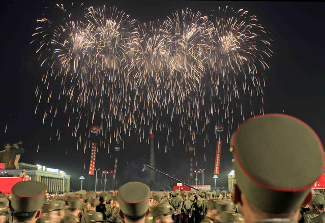 """Soldiers watch fireworks in Kim Il Sung Square in Pyongyang, North Korea, Thursday, July 6, 2017, to celebrate the test launch of North Korea's first intercontinental ballistic missile two days earlier. The North's ICBM launch, its most successful missile test to date, has stoked security worries in Washington, Seoul and Tokyo as it showed the country could eventually perfect a reliable nuclear missile capable of reaching anywhere in the United States. Analysts say the """"Hwasong 14"""" missile, tested Tuesday could reach Alaska if launched at a normal trajectory. (Photo by Jon Chol Jin/AP Photo)"""