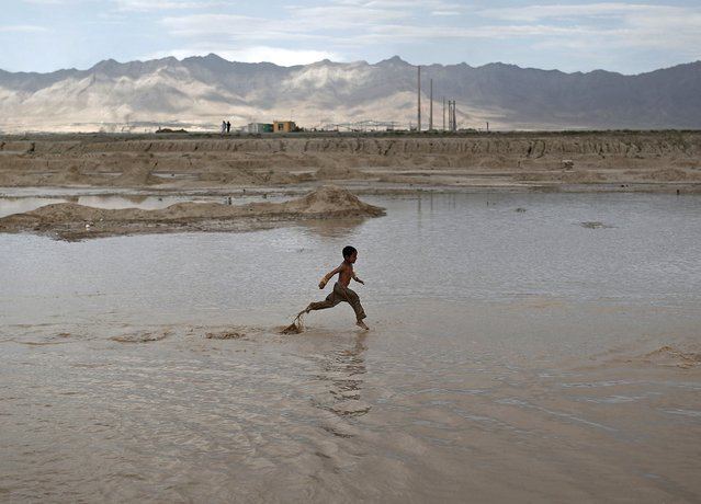 Afghan boy runs in shallow water for fun on the outskirts of Kabul city, Afghanistan July 30, 2015. (Photo by Ahmad Masood/Reuters)
