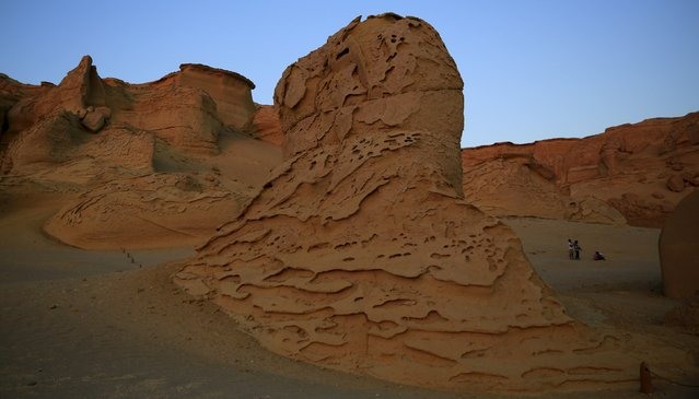 People walk around the rocks in the natural reserve area of Wadi Al-Hitan, or the Valley of the Whales, at the desert of Al Fayoum Governorate, southwest of Cairo, Egypt, August 12, 2015. Wadi Al-Hitan holds an impressive collection of fossils and bones, some of which date back over 40 million years. (Photo by Amr Abdallah Dalsh/Reuters)