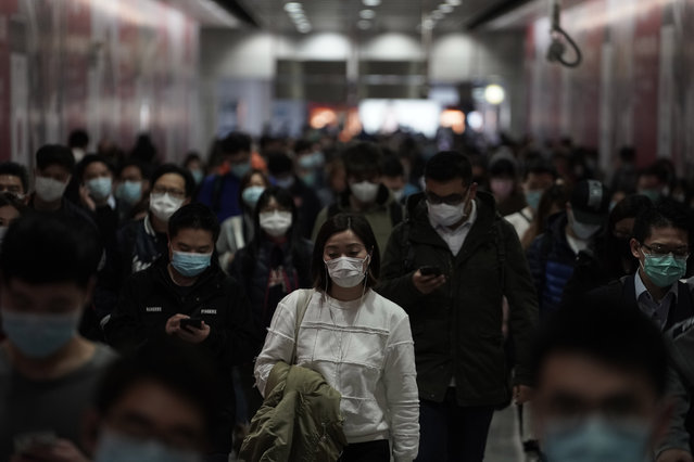 People wearing masks, walk in a subway station, in Hong Kong, Friday, February 7, 2020. Hong Kong on Friday confirmed 25 cases of a new virus that originated in the Chinese province of Hubei. According to the latest figures, 233 new cases of the novel coronavirus have been confirmed globally, Hong Kong's Chief Secretary for Admissions told a news conference. (Photo by Kin Cheung/AP Photo)