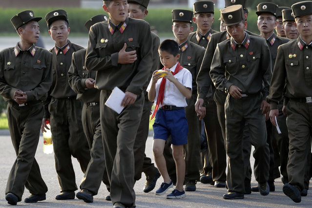 A school boy walks among soldiers at the end of a work day on Tuesday, July 25, 2017, in Pyongyang, North Korea. (Photo by Wong Maye-E/AP Photo)