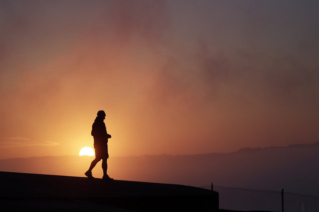 Russell Brown, of Los Altos, Calif., watches the sunrise from a a hill in the Marin Headlands on Monday, July 14, 2014, in San Francisco. (Photo by Marcio Jose Sanchez/AP Photo)