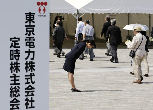 A Tokyo Electric Power Co (TEPCO) employee bows deeply as shareholders enter the venue of the company's annual general shareholders meeting in Tokyo on July 1, 2012