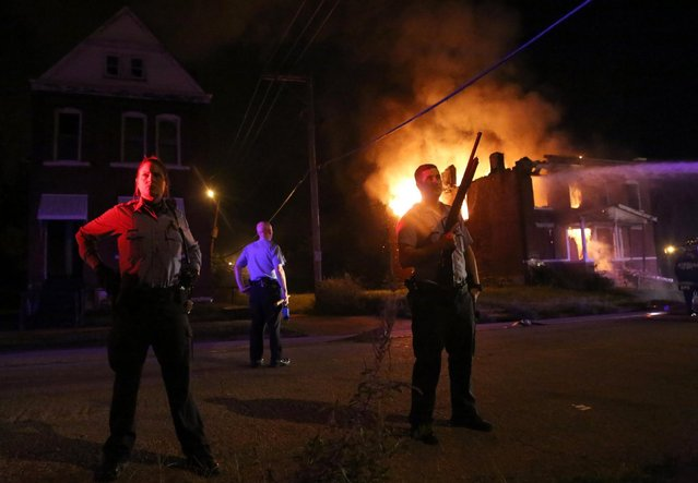 Police stand guard as firefighters extinguish a vacant house that was set on fire during protests following a fatal officer-involved shooting Wednesday, August 19, 2015, in St. Louis. A black 18-year-old fleeing from officers serving a search warrant at a home in a crime-troubled section of St. Louis was fatally shot Wednesday by police after he pointed a gun at them, the city's police chief said. (Photo by Laurie Skrivan/St. Louis Post-Dispatch via AP Photo)