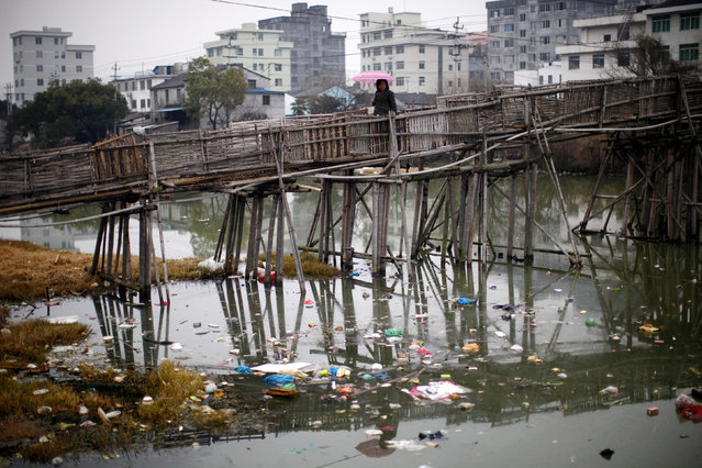A woman walks on a bridge over a polluted river at a suburban area of Wenzhou, in Zhejiang province February 18, 2011. China is now the world's second largest economy, but hundreds of millions of its people still rely on fouled water that will cost billions of dollars to clean. Growing cities, overuse of fertilisers, and factories that heedlessly dump wastewater have degraded China's water supplies to the extent that half the nation's rivers and lakes are severely polluted. (Photo by Carlos Barria/Reuters)