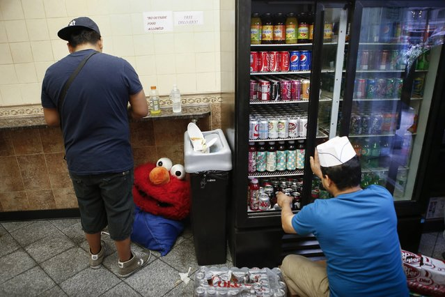 Jorge, an immigrant from Mexico, who works for tips dressed as the Sesame Street character Elmo takes a lunch break in Times Square, New York July 30, 2014. (Photo by Eduardo Munoz/Reuters)