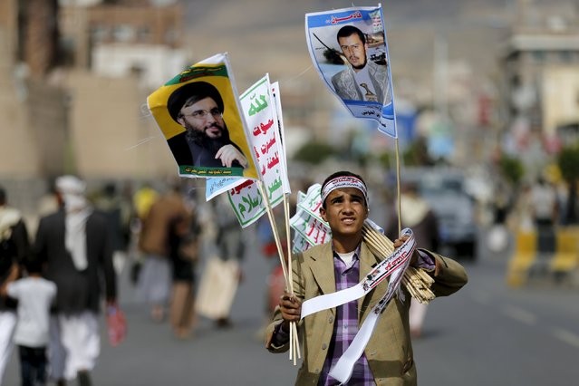 A boy sells flag posters of Lebanon's Hezbollah leader Sayyed Hassan Nasrallah (L) and Yemen's Houthi leader Abdul Malik al-Houthi ahead of a demonstration by Houthi followers against the Saudi-led air strikes in Yemen's capital Sanaa August 24, 2015. (Photo by Khaled Abdullah/Reuters)