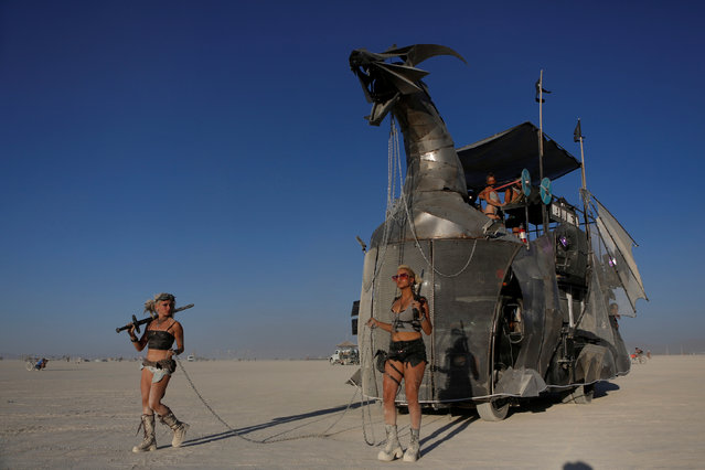 Two women escort a mutant vehicle on the playa as approximately 70,000 people from all over the world gathered for the annual Burning Man arts and music festival in the Black Rock Desert of Nevada, U.S. August 29, 2017. (Photo by Jim Urquhart/Reuters)