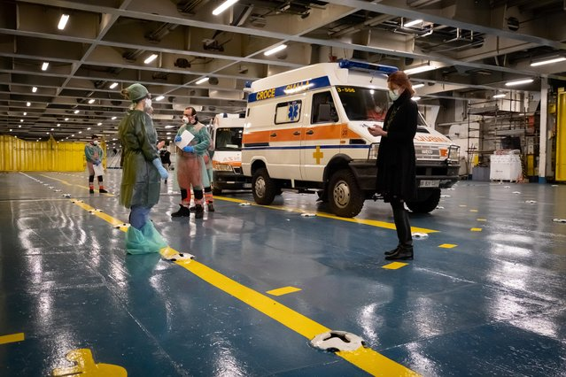 "People in medical suits, gloves and masks are seen near the ambulances on the deck of the docked ""Splendid"" passenger ship as the first coronavirus patients are transported to the ship, which has been transformed into a hospital, at the port of Genoa, Italy, March 23, 2020. (Photo by Marco Gozzi/Ufficio Stampa Regione Liguria/Handout via Reuters)"