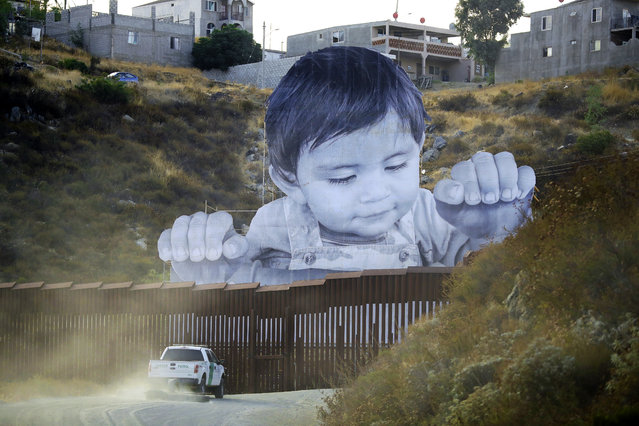 A U.S. Border Patrol vehicle drives in front of a mural in Tecate, Mexico, just beyond a border barrier in Tecate, Calif., on Friday, September 8, 2017. A French artist aiming to prompt discussions about immigration erected the 65-foot-tall image of a Mexican boy, pasting it to scaffolding built in Mexico. The installation overlooks a section of wall on the California border. (Photo by Gregory Bull/AP Photo)