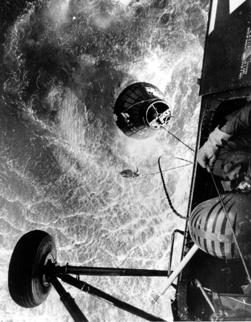 """A U.S. Marines helicopter hovers over the Atlantic ocean during an attempt to retrieve the spacecraft Liberty Bell 7, which sank 15,000 feet shortly after splashdown on July 21, 1961.  At top of the spacecraft is the """"horse collar"""" hoist which would have been used to lift astronaut Virgil """"Gus"""" Grissom, who had to swim from the craft.  The duration of the Mercury-Redstone 4 test flight, which is the second U.S. manned suborbital spaceflight, was 15 minutes and 37 seconds. (Photo by AP Photo/NASA)"""