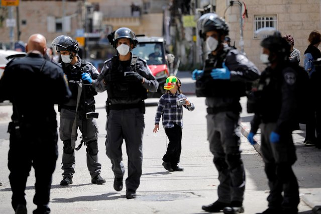 A boy wears a clown mask next to Israeli police as they patrol to enforce government restrictions set in place to curb the spread of the coronavirus disease (COVID-19), in Mea Shearim neighborhood of Jerusalem on April 6, 2020. (Photo by Ronen Zvulun/Reuters)