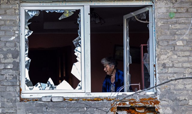 An elderly woman stands behind broken glass in her apartment damaged after Ukranian army shelling downtown of Donetsk, Ukraine, 20 August 2014. Thirty-four people have been killed in fighting between separatist militants and government troops in Ukraine's eastern Donetsk region over the past 24 hours, the local government said. (Photo by Sergei Ilnitsky/EPA)