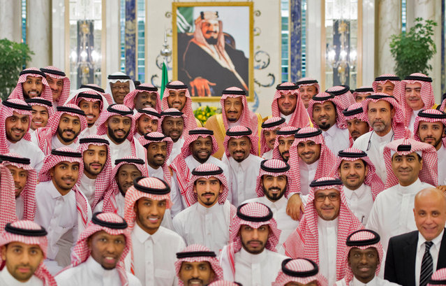A handout picture provided by the Saudi Royal Palace on September 20, 2017 shows King Salman bin Abdulaziz Al Saud (C) posing in a group picture with members of the Saudi national football team, at a welcoming ceremony at the Royal Palace in Jeddah. (Photo by Bandar Al-Jaloud/AFP Photo/Saudi Royal Palace)