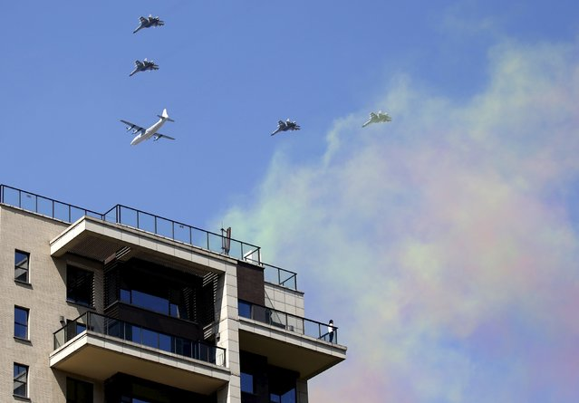 A woman watches military aircraft perform from a balcony of an apartment during the military parade to mark the 70th anniversary of the end of World War Two, in Beijing, China, September 3, 2015. (Photo by Kim Kyung-Hoon/Reuters)